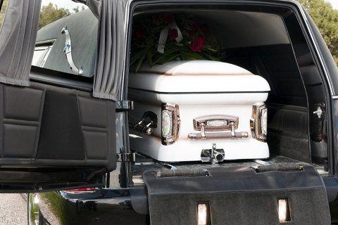 Bara bianca con ornamenti cromati e coperto di rose rosse all'interno del carro funebre