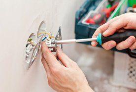 A person fixing a plug socket