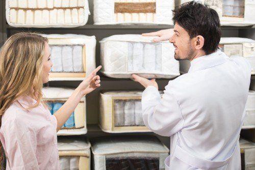 una donna indica al commesso il materasso scelto