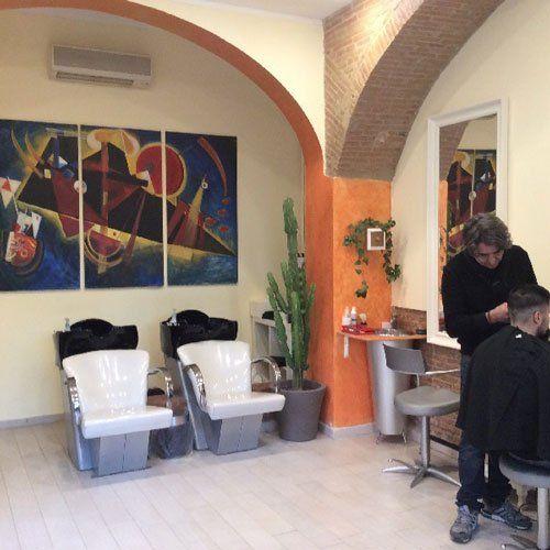 un parrucchiere che sta tagliando i capelli a un uomo e vista di due seggiolini bianchi con dei lavandini neri per lavare i capelli