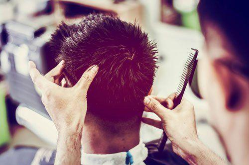 due mani di un parrucchiere con in mano un pettine e di fronte un ragazzo seduto visto da dietro