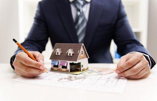 consulente stila un documento con sopra un modellino di casa e delle chiavi