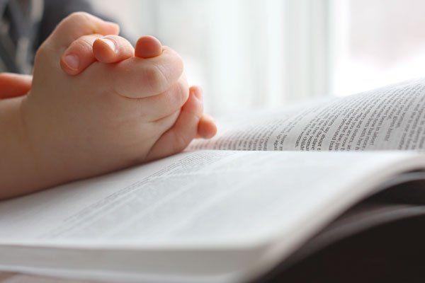 mani di bimbo mentre leggono un libro