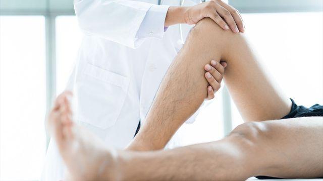 fisioterapista maschio massaggiare la gamba del paziente in una stanza fisio