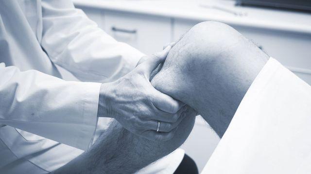 Traumatologo chirurgo ortopedico medico di controllo, uomo di mezza età paziente per determinare lesioni
