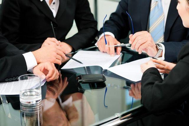 delle persone vestite con dei completi formali e degli occhiali da vista in mano discutono di lavoro alla scrivania