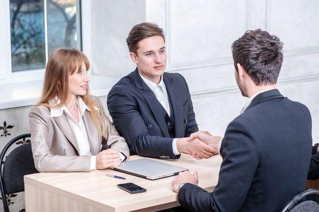 un uomo affianco ad una donna sta stringendo la mano a un consulente
