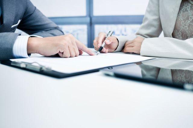 un uomo indica un foglio e una donna lo firma