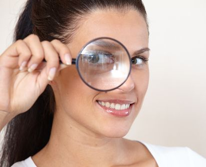 Lady seeing through magnifying glass