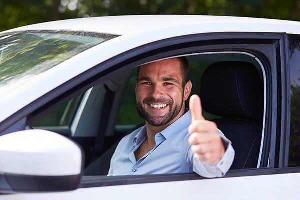un uomo in macchina con il pollice in su