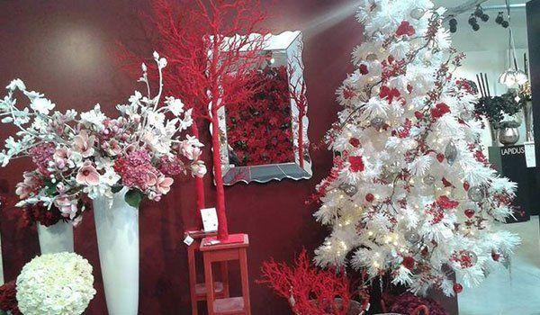 Interno del negozio, articoli di decorazione di color bianco e rosso, albero di natale di color bianco con fiocchi rossi, muri rossi e vasi bianchi con dei fiori