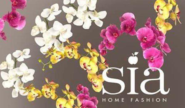 Fiori rosa, bianchi e gialli e una scritta SIA Home Fashion con una mela sulla i