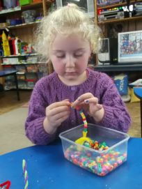 Girl playing with beads at childcare centre