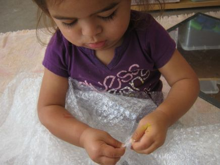 Girl playing with bubble wrap