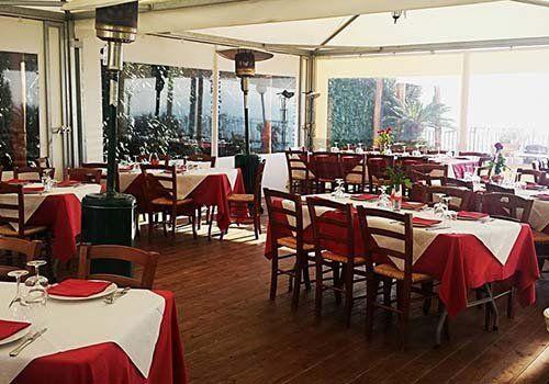 Vista generale del ristorante con le tavole preparate in colori bianco e rosso e con stufe per combattere il freddo