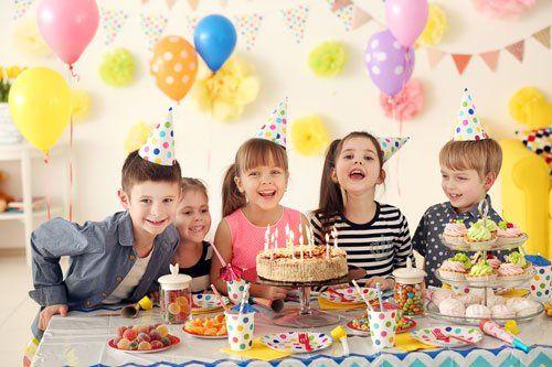 Bambini felici celebrando un compleanno, torta, pastelli,aerostati,bevande,dolci...