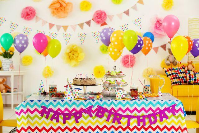 Tavola con happy birthday sul fronte e coperta con le bevande,dolci,cibo e la torta in una camera di colori piena di aerostati