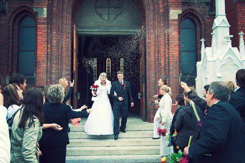 Gente lanciando riso sui sposi novelli che stanno uscendo della Chiesa