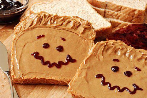 Pane corrotto con burro di arachidi e con una faccia delineata con sciroppo di cioccolato
