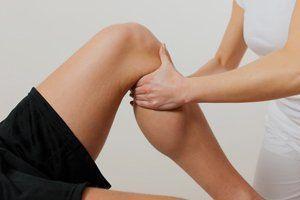 A therapist massaging a patient's lower leg