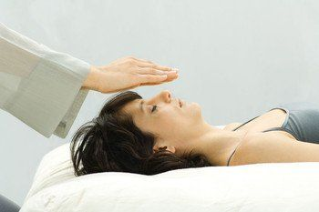 Therapist's hands above the head of a patient lying on her back