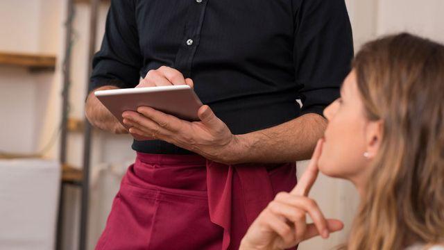 Cameriere prende l'ordinazione da una ragazza indecisa