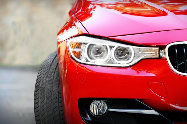 Faro anteriore sinistro di un'automobile rossa
