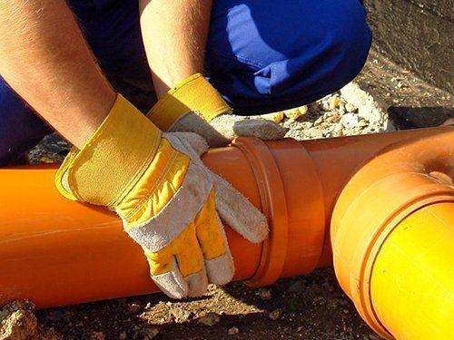operaio con guanti durante montaggio tubi acqua in un cantiere