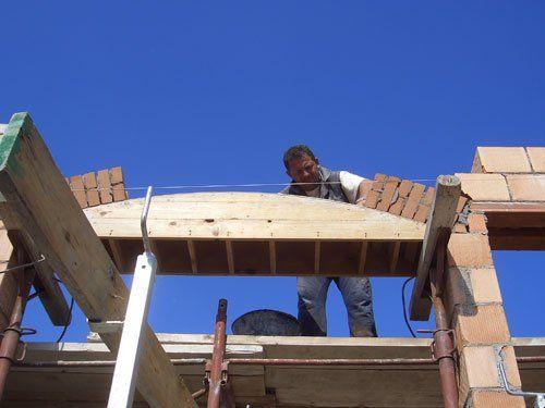 operaio mette in posa dei mattoni sul tetto di una casa