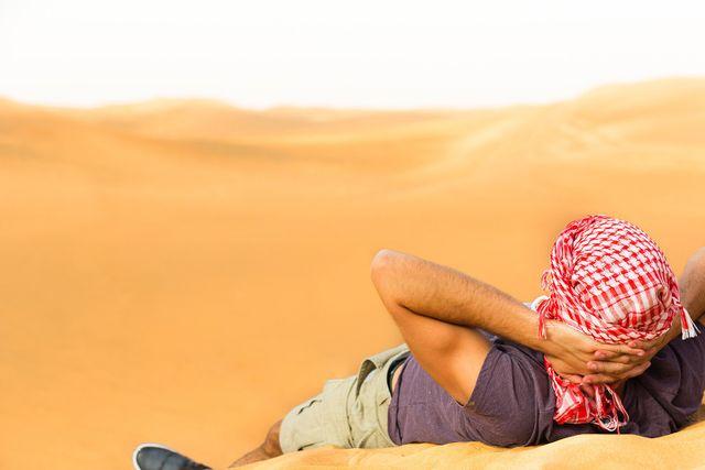 Giovane disteso sulla sabbia che guarda il deserto