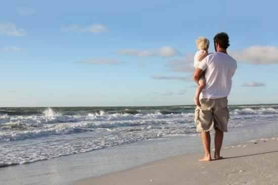 un ragazzo con in braccio un bambino sulla riva del mare