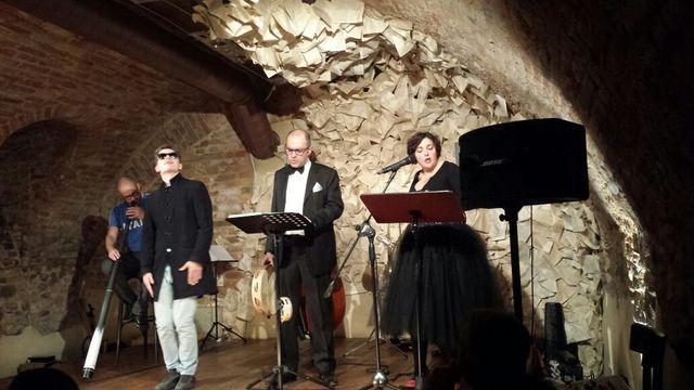 un uomo che sta recitando sul palcoscenico con un microfono e di fronte l'ombra di una spettatrice al tavolo