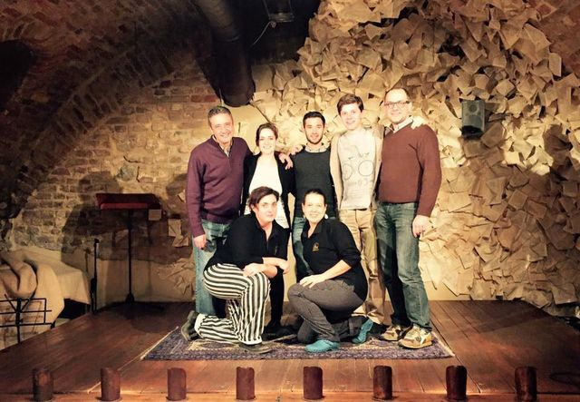 persone sul palco in piedi e in ginocchio su un tappeto in posa per una foto