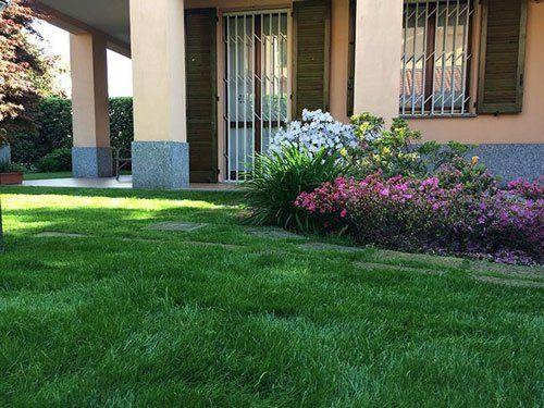 Una villa e vista ravvicinata del prato e piante fiorite