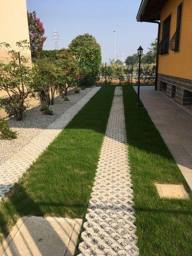 Aiola lunga con dei alberi e terreno coperto con sassi bianchi e strisce di prato e pavimentazione