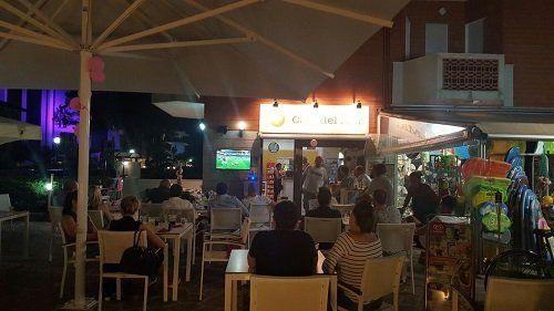delle persone sedute all'esterno vicino a un ombrellone mentre guardano una partita in tv