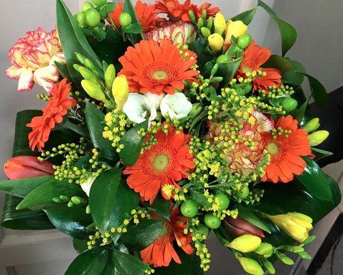 un bouquet con fiori misti gialli e arancioni