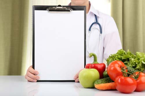 medico mostra un blocco note vicino a delle verdure