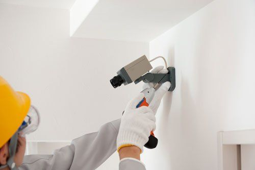 un uomo con un elmetto giallo e con in mano un trapano avvitatore sta installando una videocamera di sorveglianza