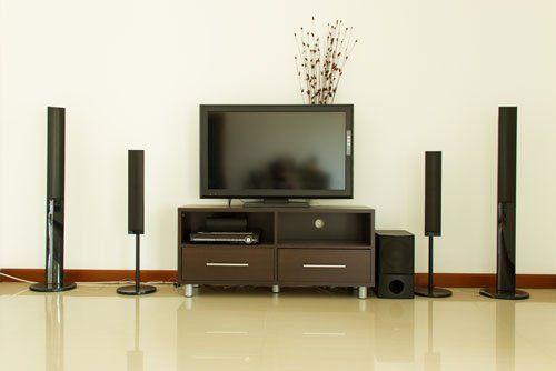 un televisore di color nero con sotto un mobiletto e accanto un impianto home theater