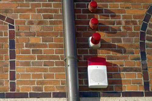 una facciata di uno stabile in mattoni arancioni, un tubo di una grondaia e accanto un dispositivo di allarme con la sirena