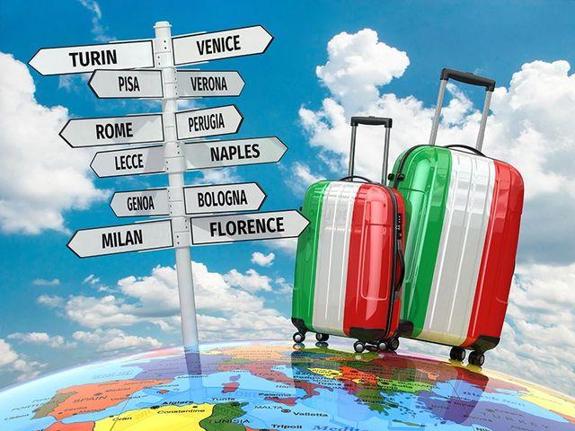 dei cartelli con dei nomi di città importanti e due trolley in tema bandiera italiana