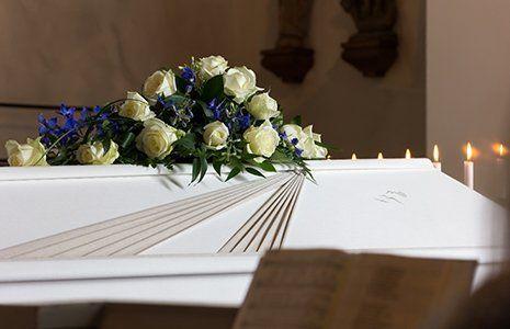 Dettaglio di un feretro con fiori bianchi e candele