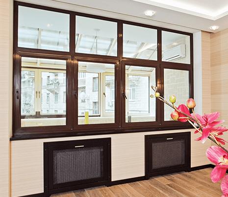 vista di una serie di finestre color marrone rifinite in pvc e sotto dei termosifoni coperti da delle griglie
