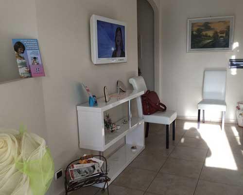 una sala d'attesa con due sedie e una Tv al muro