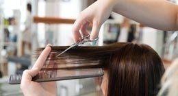 Parrucchiera taglia i capelli di una cliente