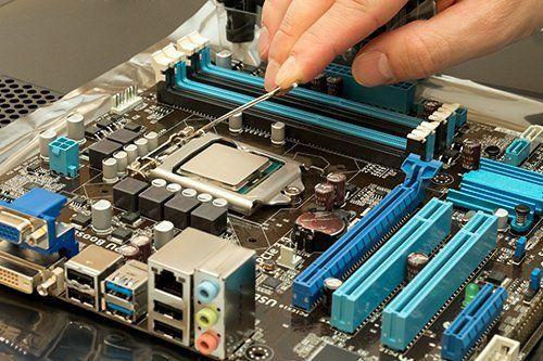 Killa-Byte technician repairing a computer's motherboard