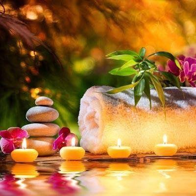 un asciugamano bianco arrotolato con sopra un fiore rosa,  accanto dei sassolini messi uno sopra l'altro, dei petali rosa e dei lumini gialli accesi a Cassano Magnago, VA