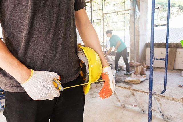 un muratore con un elmetto giallo in mano e un metro