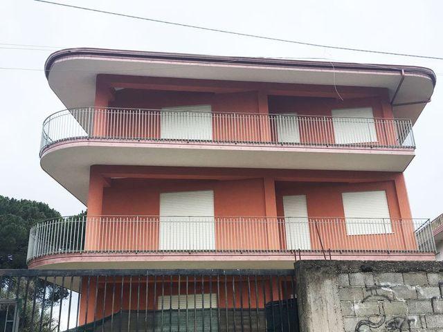 un condominio rosa a tre piani